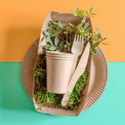 ECO craft paper tableware. Paper cups, plates, bag, fast food containers and wooden Cutlery with cornstarch on a colored orange-blue background. Recycling or the concept of zero waste. The view from the top.